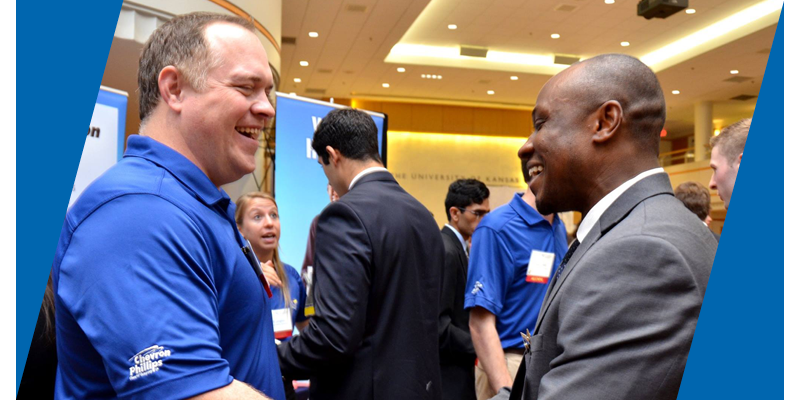 A man in a blue polo shirt smiles as he shakes hands with a student wearing a suit, also smiling. In the background, other students and employers engage at a career fair.