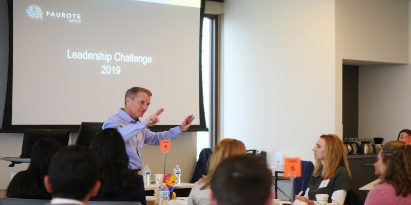 A man, Denny Faurote, speaks to a room of students and employers. The screen behind him says Leadership Challenge 2019.