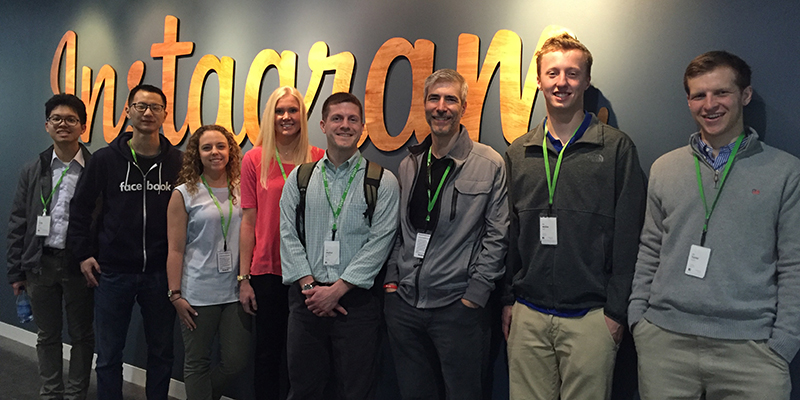 A group of eight smiles at the camera as they stand in front of a grey wall with the Instagram logo written in giant cursive letters behind them.